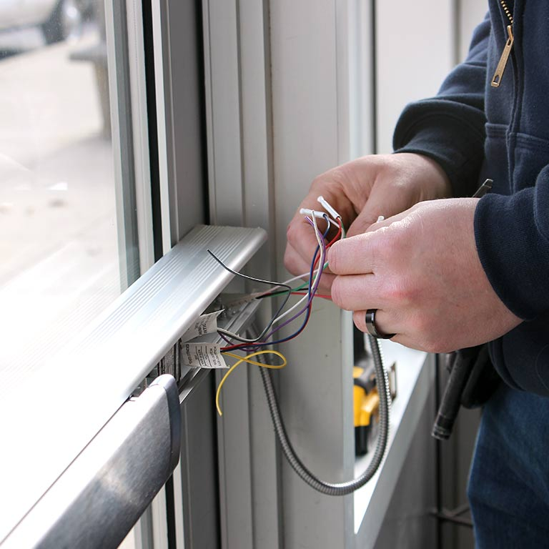 A person manipulates wires for a security system attached to a window.