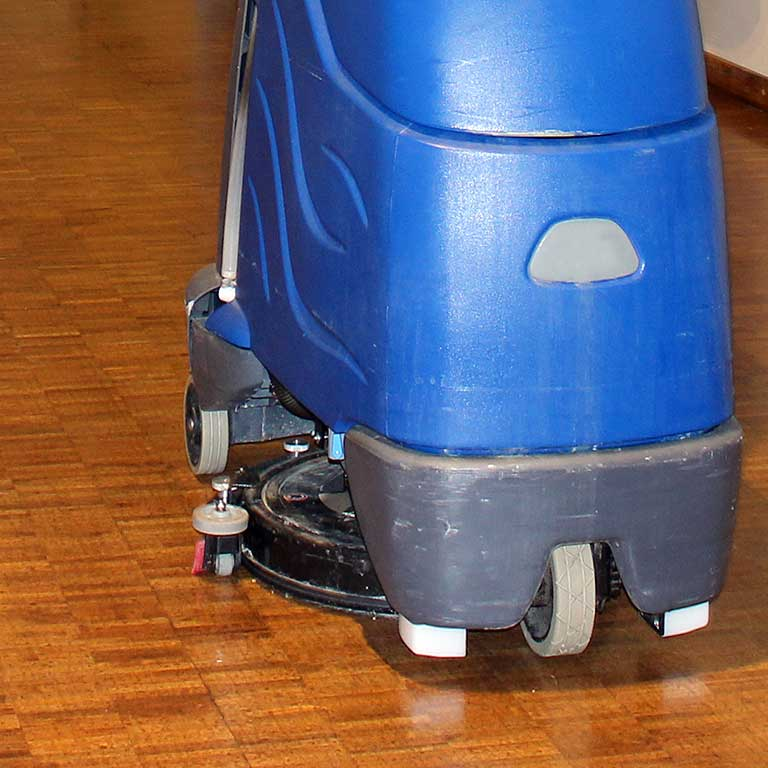 A floor cleaning machine cleans a wood floor.