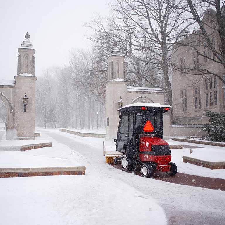 A small vehicle with a snowplow clears snow from in front of the Sample Gates.